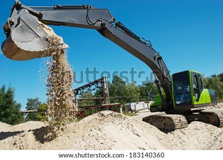 excavator machine at excavation work in sand quarry - stock photo