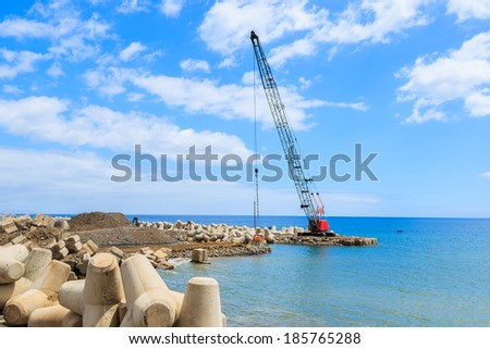Excavator machine building new harbour on coast of Madeira island, Portugal - stock photo