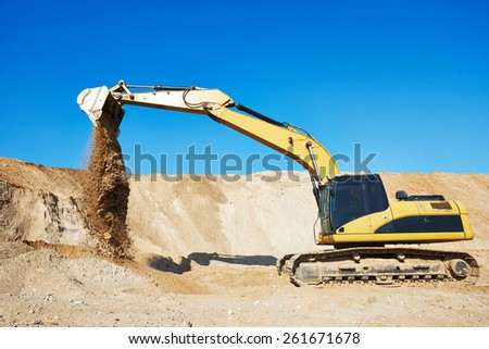excavator machine doing excavation earthmoving work in sand quarry - stock photo