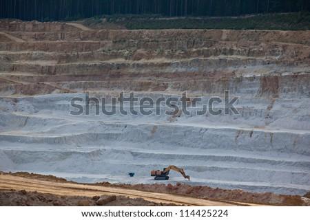 Excavator mining layer of glass sand - stock photo