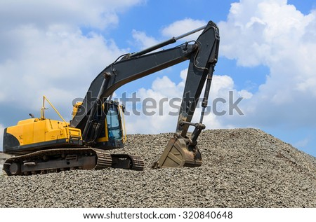 Excavator on Stone Drum against blue cloudy sky - stock photo