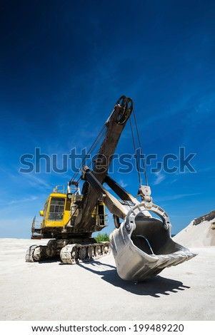 Excavator on the background of of blue sky and gravel - stock photo