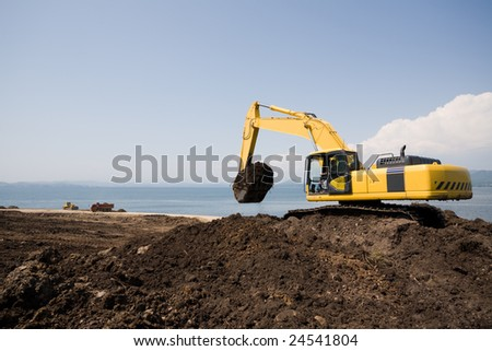 Excavator on the workplace on a background of the sea.