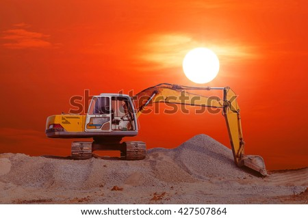 Excavator parked on the mound with colorful sunset and red sky background. - stock photo