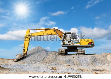 Excavator parked on the mound with the beautiful sky and sunlight.