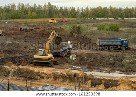 Excavator pours soil into the back of the truck. - stock photo