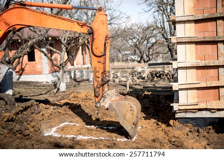 excavator scoop on construction site, digging earth and loading dumper trucks.  - stock photo