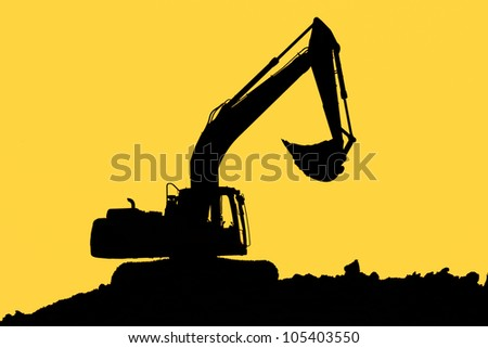 Excavator standing in a ground with raised bucket over cloudscape sky - stock photo