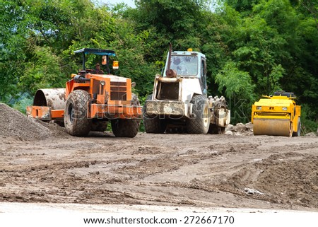 Excavator with backhoe unloading sand at eath works in construction site to the road. - stock photo