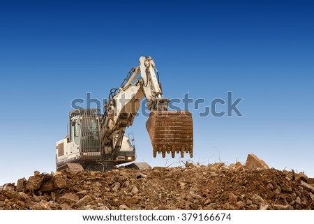 excavator with bucket on gravels blue sky background - stock photo