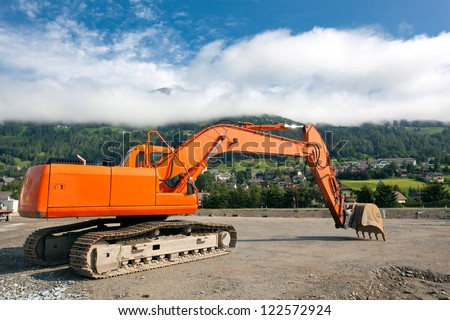 Excavator with metal tracks at construction site on austrian alps background - stock photo