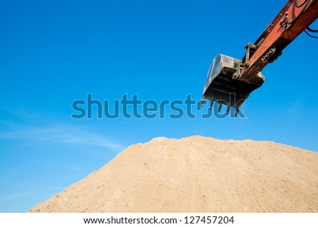 Excavator working at sandpit. Scoop close-up - stock photo