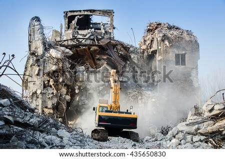 Excavator working at the demolition of an old industrial building. - stock photo