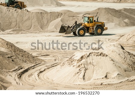 excavator working on sand dunes - stock photo