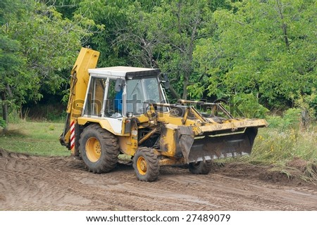 Excavator working on the field - stock photo