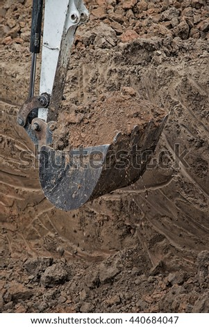 Excavator working with red soil.