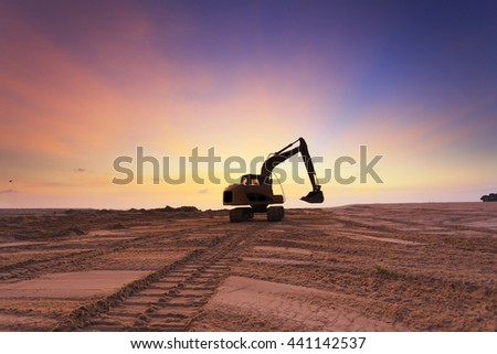 excavators dinging sand at beach silhouette