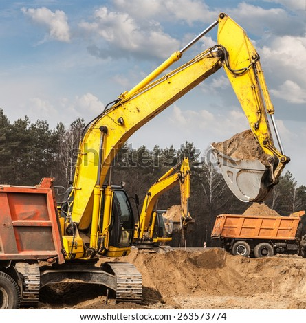 Excavators ship sand in trucks on road construction - stock photo