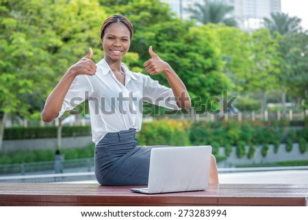 Excellent and successful business in Dubai. Smiling African businesswoman businessman sitting in the street and working at a laptop in Dubai downtown showing thumbs up with both hands - stock photo
