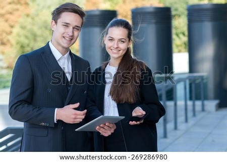 Excellent business cooperation. Portrait of two confident and motivated partners. Man and woman are discussing details of current project. Outdoor business concept