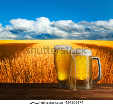 excellent light beer on a wooden table in a landscape - stock photo