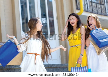 Excellent shopping. Three young and pretty girls are standing with shopping bags and smiling. All are in a great mood while shopping - stock photo