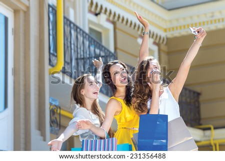 Excellent smile on the mobile phone. Three young and pretty girls are standing with shopping bags and taking photos on mobile phone. Mood is just great because of shopping - stock photo