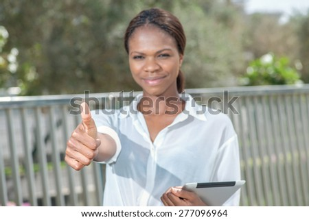Excellent work. African businesswoman businessman holding a tablet in her hand while standing on the street and looking into the camera showing a thumbs up - stock photo