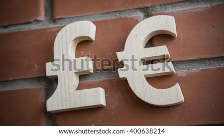 Exchange currency euro and pound on a brick wall - stock photo