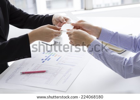 Exchanging business cards in the office - stock photo