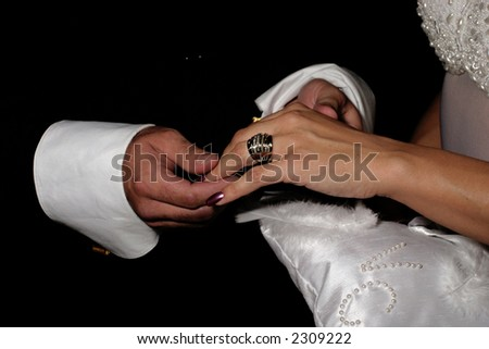 Exchanging rings over a white pillow at a wedding