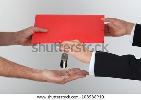 Exchanging signed contract for keys - stock photo