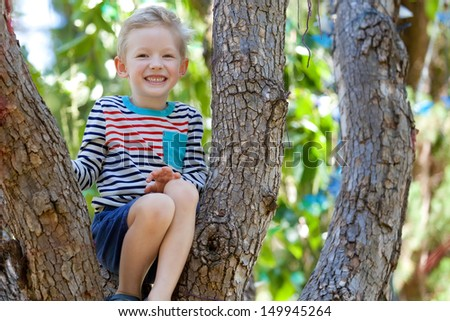 excited adorable boy sitting at the branch of the tree - stock photo