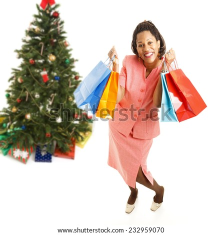 Excited african-american woman, holding shopping bags.  Full body isolated on white with Christmas tree in background.  .