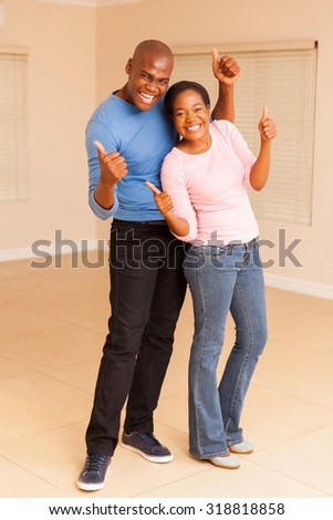 excited african couple giving thumbs up and celebrating in their new house - stock photo