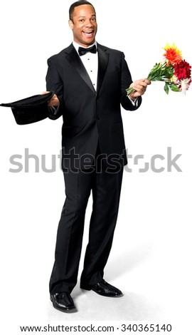 Excited African man with short black hair in evening outfit holding flowers - Isolated