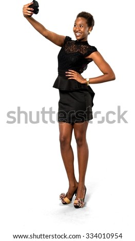Excited African young woman with short dark brown hair in evening outfit using camera - Isolated