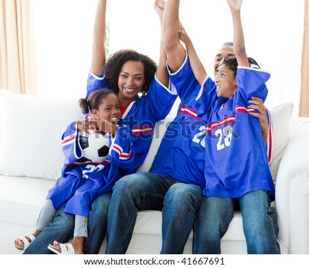Excited Afro-American family celebrating a goal - stock photo