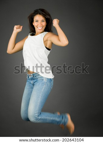 Excited and cheerful young woman jumping in air and smiling - stock photo