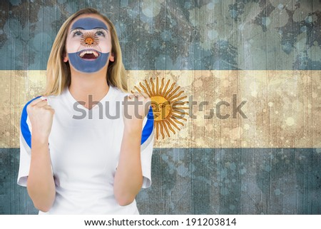 Excited argentina fan in face paint cheering against argentina flag in grunge effect - stock photo