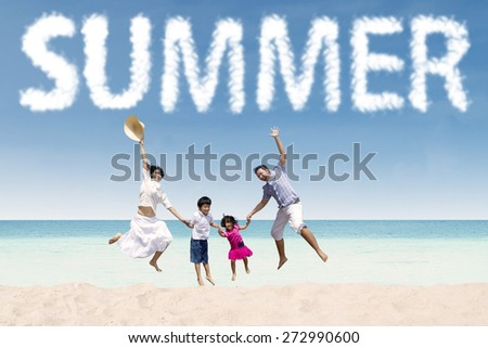 Excited asian family jumping on the tropical seaside under a summer's cloud - stock photo