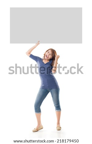 Excited Asian girl hold a blank board, full length portrait isolated on white. - stock photo