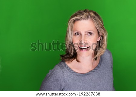 Excited attractive middle-aged woman turning towards the camera with a smile of delight on a green background with copyspace - stock photo