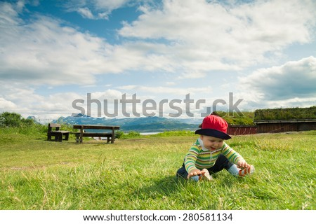 Excited baby playing with the grass with fjords and mountains in the background