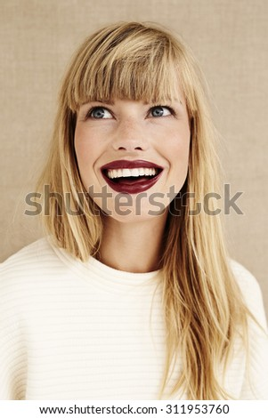 Excited beautiful blond woman looking up - stock photo