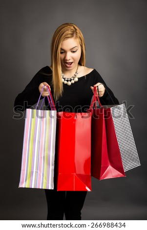 Excited beautiful girl looking into her shopping bags over gray.Consumerism concept - stock photo