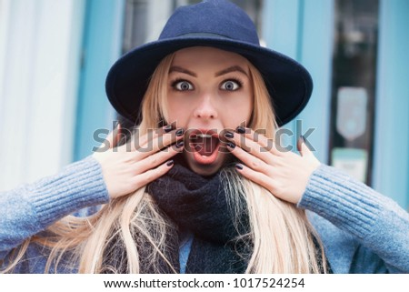 Excited beautiful lady in hat and blue dress looking camera with opened mouth and smiling.Shocked and surprised girl outdoor.