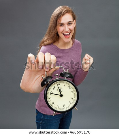 excited beautiful woman raising an alarm clock in her oversized hand for focus on optimism and winning deadline management in the foreground