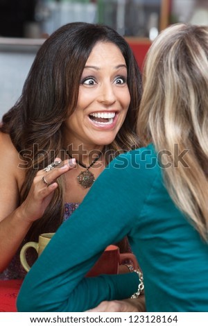 Excited beautiful woman talking to friend in restaurant - stock photo