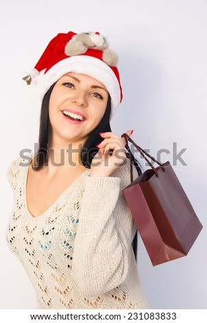 Excited beautiful young Caucasian brunette woman shopping for Christmas wearing Santa hat, over white